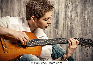 guitar music - Romantic young man playing an acoustic...