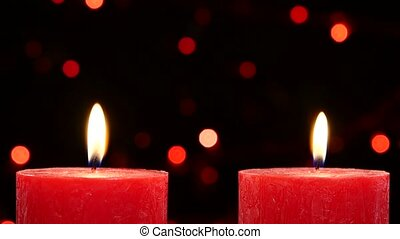Two red candles with christmas decorations on black, bokeh,...