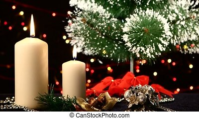 Two white candles with christmas decorations and tree on...