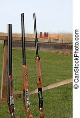 Shotguns on a rack at a shooting range.