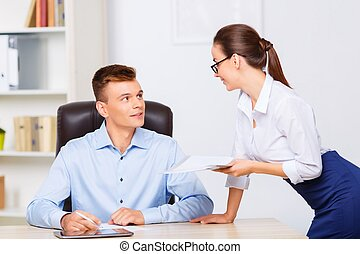 Attractive assistant brings paperwork for her boss. -...