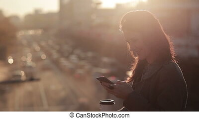 beautiful girl uses a smartphone on a city bridge