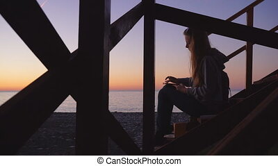 Travel: Silhouette of beautiful girl tourist drawing sunset...
