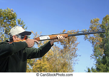 Man Bird Hunting - Man shooting a shotgun Bird hunting or...