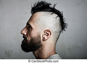 Portrait of a bearded man with mohawk. Concrete background -...