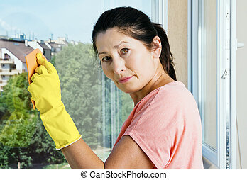 Woman washes a window - Asian woman cleaning a window with...