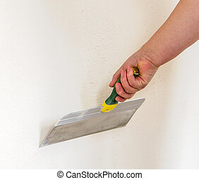 putty knife - home improvement - putty knife in hand