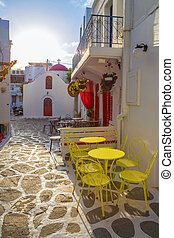Mykonos streetview at sunrise with chapel and yellow chairs...