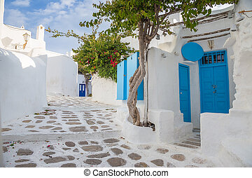 Mykonos streetview with blue door and trees, Greece