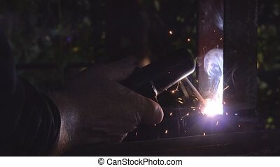 Worker arc welding in workshop, male welder using electrode...