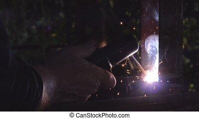 Worker arc welding in workshop, male welder using electrode...