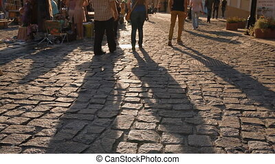 Long shadow of walking in sunset light people on...