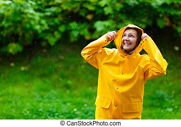 Girl under rain - Happy young woman in yellow raincoat under...