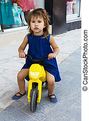 Little girl with tricycle - Portrait of a playful little...