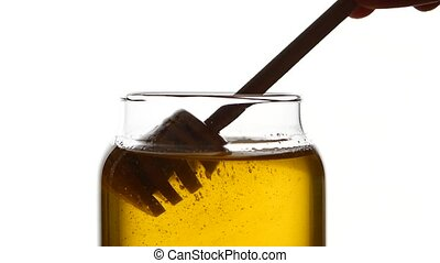 Glass jar of honey with wooden spoon, pick it up, isolated...