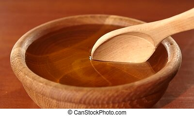 Taking honey by using spoon in wooden bowl, slow motion -...