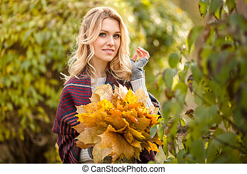 Blond woman with bouquet from maple leaves - Cute blonde...