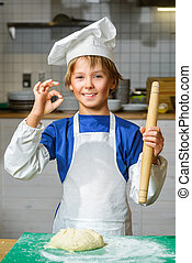 Funny happy chef boy cooking at restaurant kitchen or...