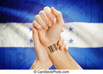 Barcode ID number on wrist and national flag on background -...