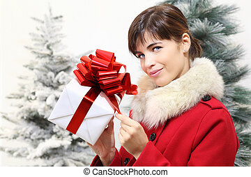 woman with Christmas gift box, looks ahead, with trees in the background