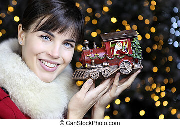 Christmas woman smiling with train toy on lights background