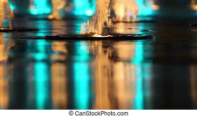 reflections of colorful fountain at night close-up