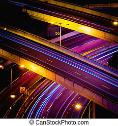 Abstract night view of highway interchange with moving cars....