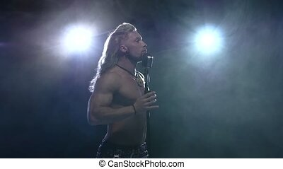 Handsome muscular man sings into microphone.  Slow motion, smoke