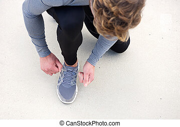 Man tying shoelace on sports shoes from above