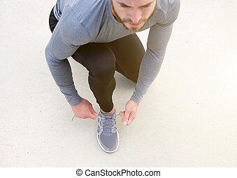 Man tying sport shoe shoelace - Portrait of a man tying...
