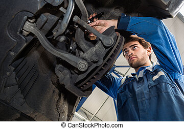 Mechanic Repairing Car In Automobile Shop