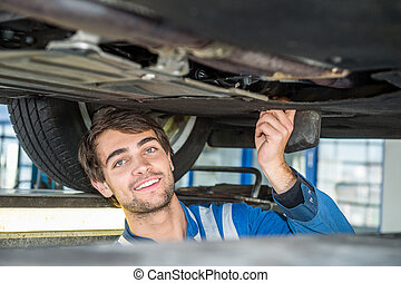 Smiling Female Mechanic Holding Car Tire