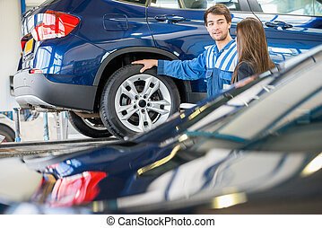 Mechanic And Customer Discussing Problem With Car