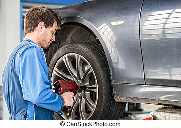 Mechanic Changing Wheel On Car With Pneumatic Wrench - Male...