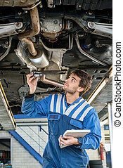 Mechanic Examining Exhaust System Of Car With Flashlight -...