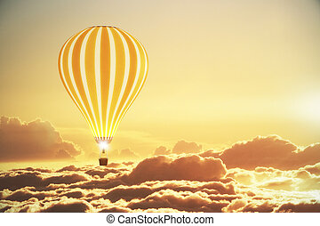 Balloon above the clouds at sunset