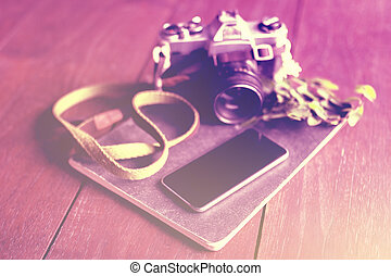 Blank smartphone screen, old style camera and diary on...