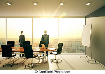 Businessmen in sunny conference room with furniture and...
