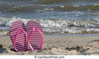 Pink flip flops blurred, against the backdrop of the waves,...