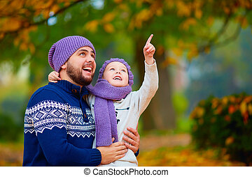 happy father and son spending time together in autumn park