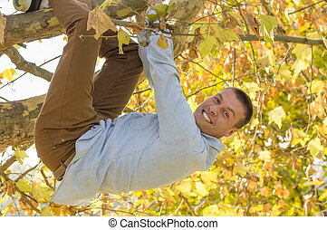 Smiling handsome man hanging from the tree