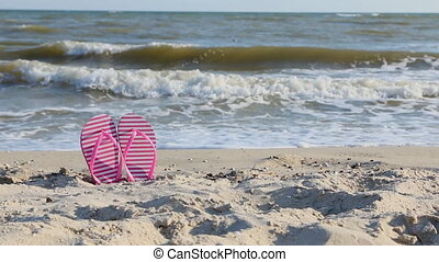 Panorama pink flip flops on yellow sandy beach near sea...