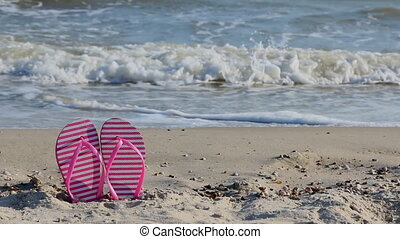 Pink flip flops on yellow sandy beach near sea waves, nobody...