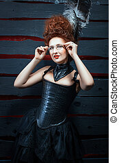 Old-fashioned girl in a corset and high hairdo Her hair...