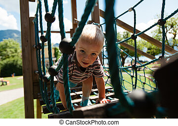 The boy on the playground - Little boy overcomes climbing...