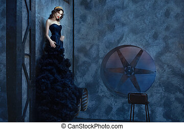Woman in a long black dress standing dark room - Woman in a...