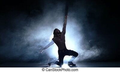 Night club dancers, muscles man silhouette of a young man dancer on the floor. Slow motion, smoke