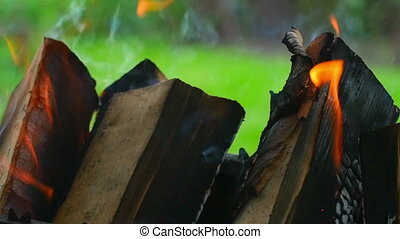 Wood burning in the brazier, outdoor close-up, slow motion