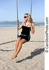 Girl on swings - Blonde girl on swings on the sand beach