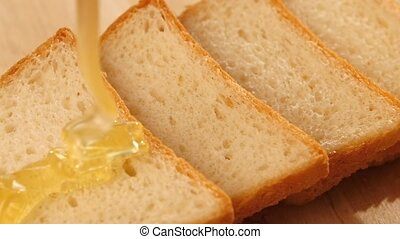 Toasted bread with flowing down honey on wooden bred, slow motion